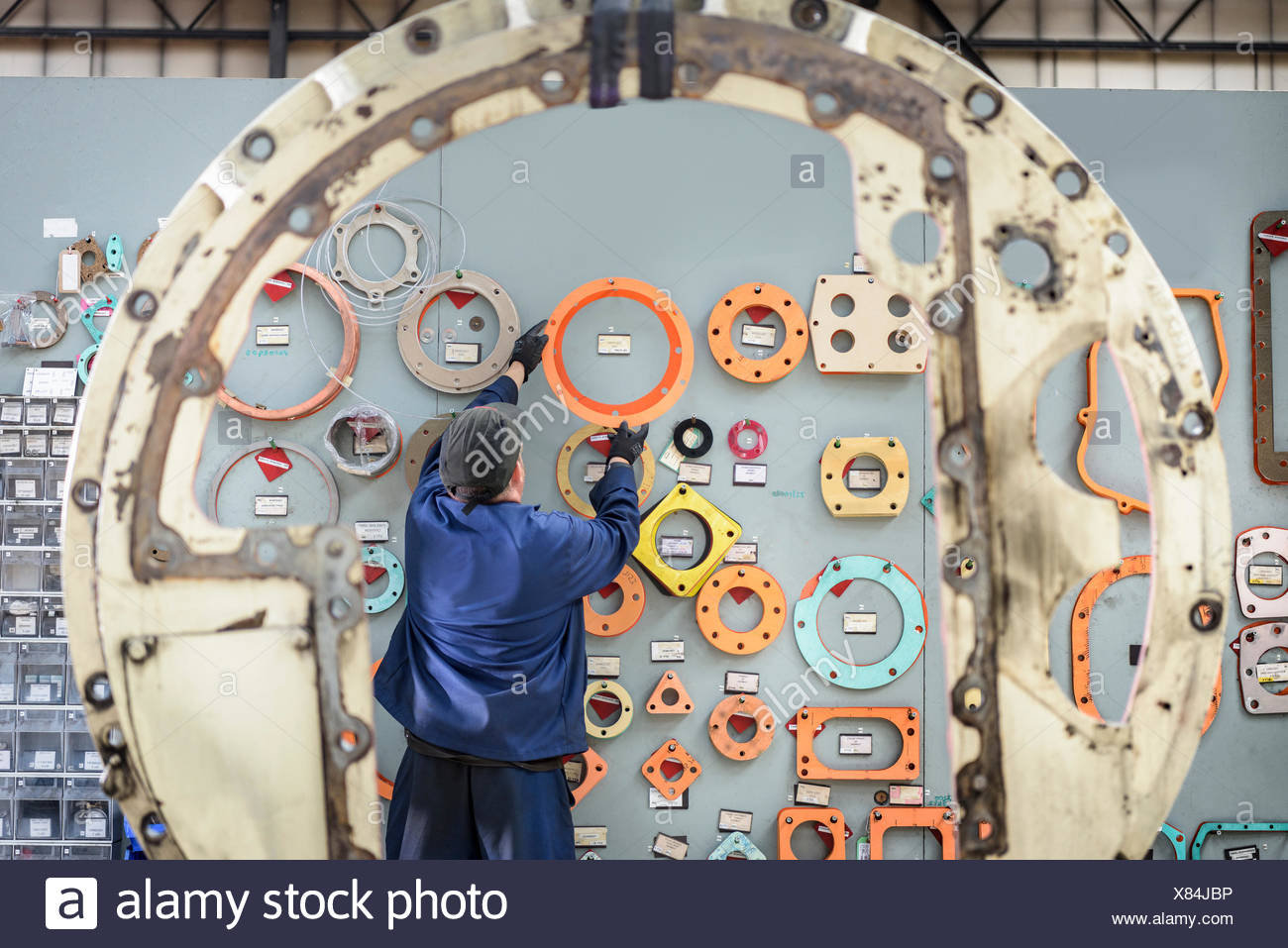 Locomotive engineer picking gaskets and seals in train works - Stock Image