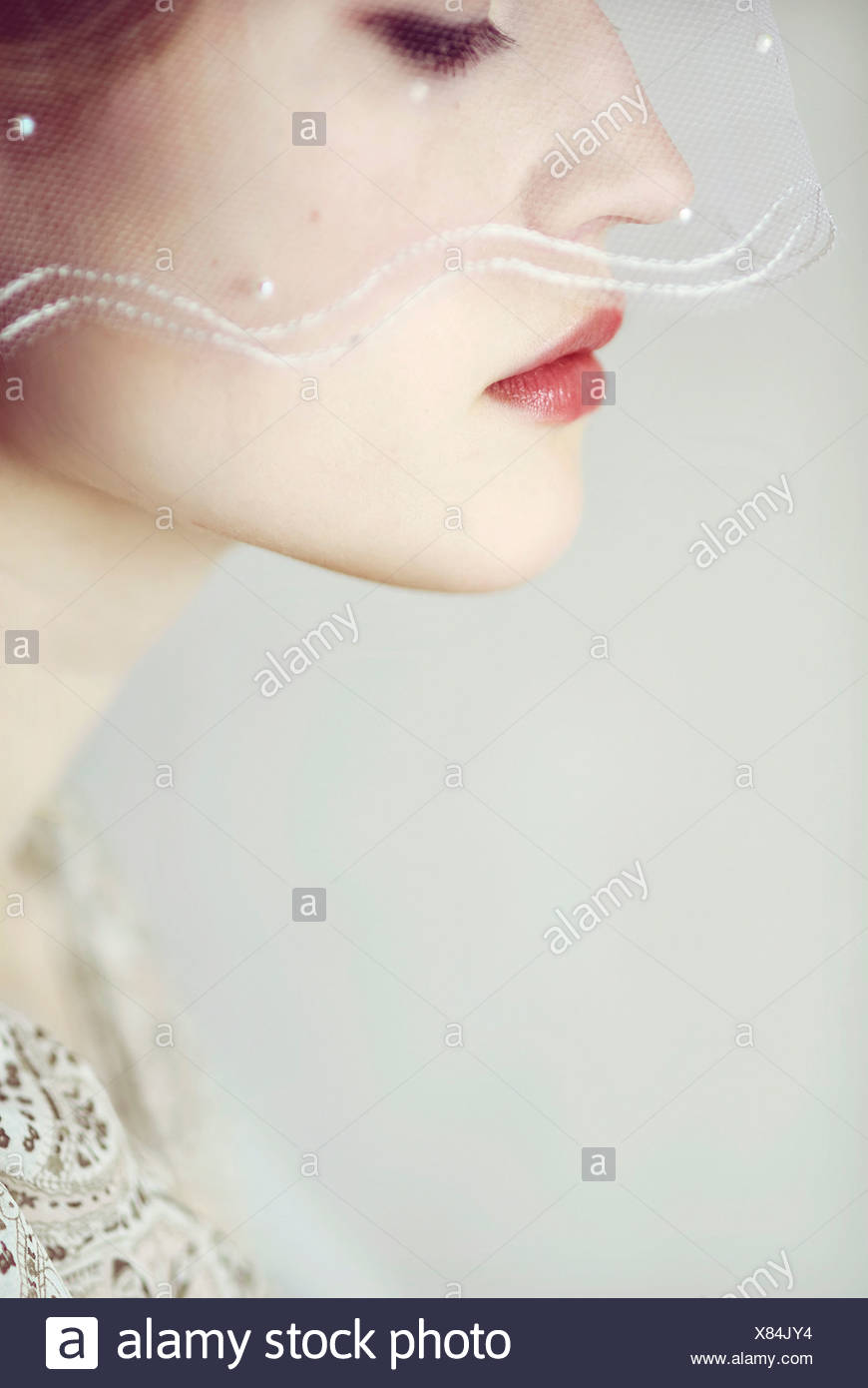 Close portrait of young woman looking down to the side with a bridal veil covering parts of her face - Stock Image