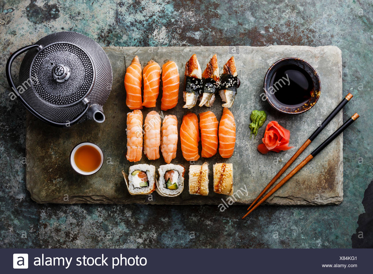 Sushi Set with tea served on gray stone slate on metal background - Stock Image