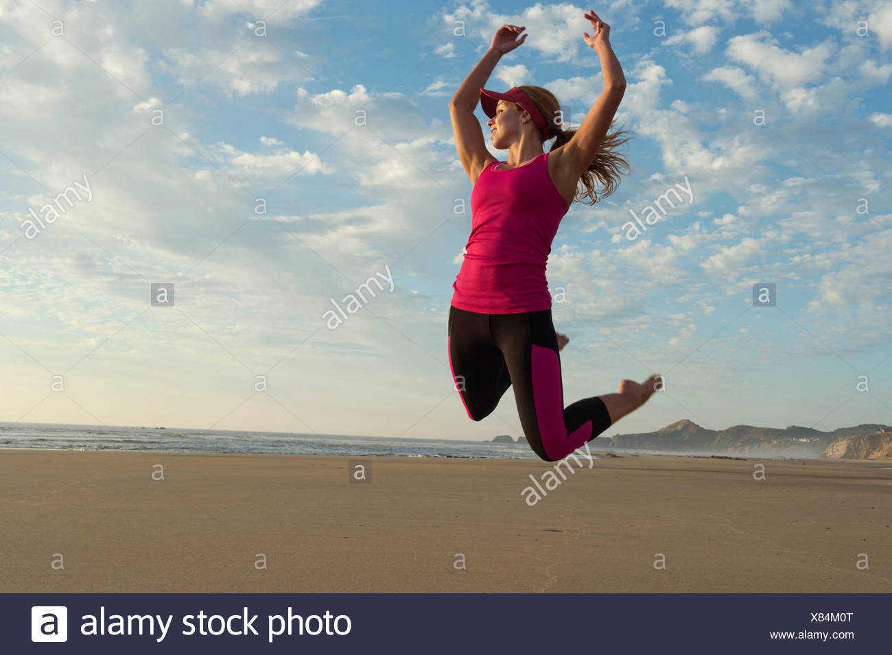 Young woman jumping in the air on beach - Stock Image