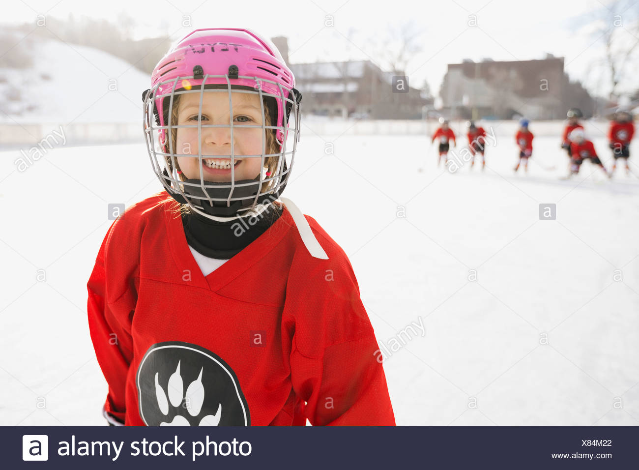 Portrait of smiling girl in ice hockey uniform - Stock Image