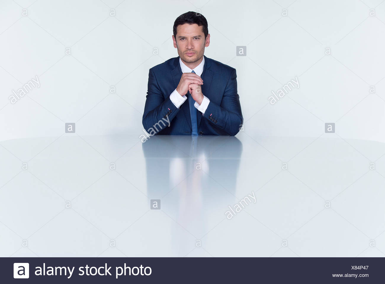Confident businessman seated at table, portrait - Stock Image