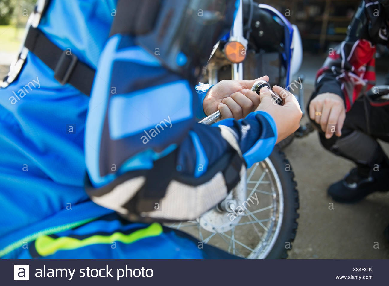 Girl using socket wrench, fixing motorbike Stock Photo