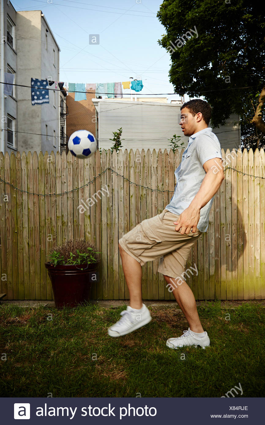 Young man kicking football in garden - Stock Image
