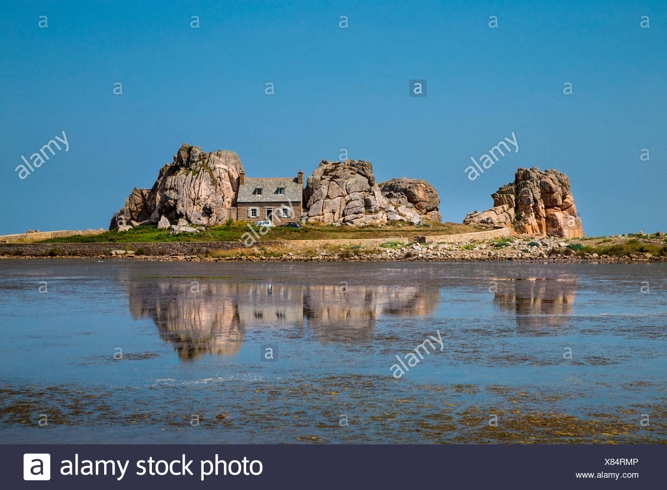 Bretagne, France. The famous house surrounded by rocks, reflecting itself in the sea. - Stock Image