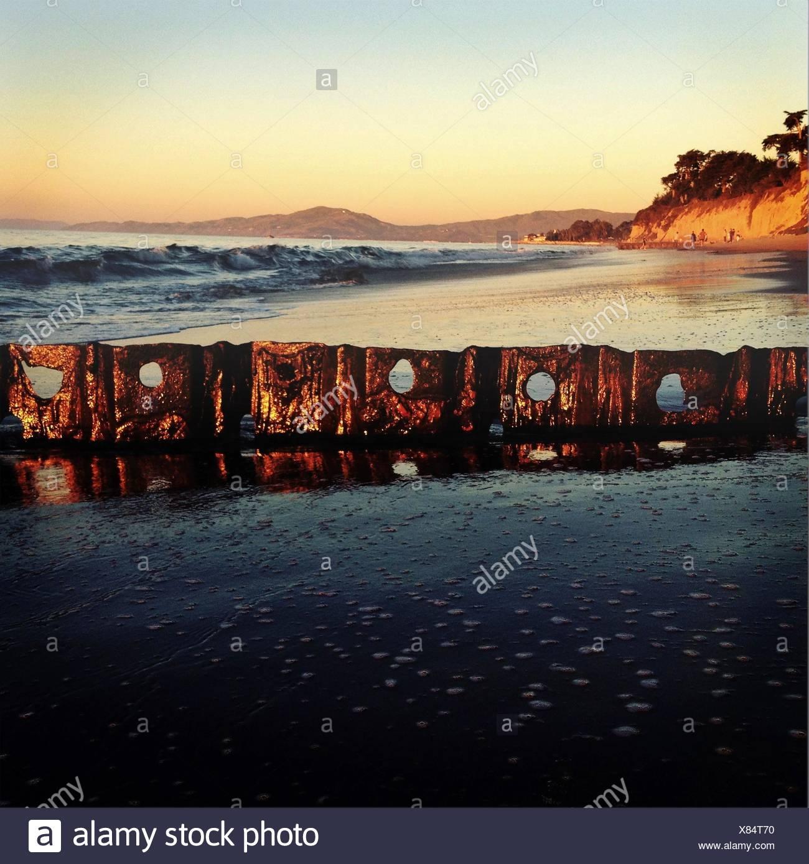 USA, California, Santa Barbara, Ruin of jetty at Butterfly Beach at sunset - Stock Image