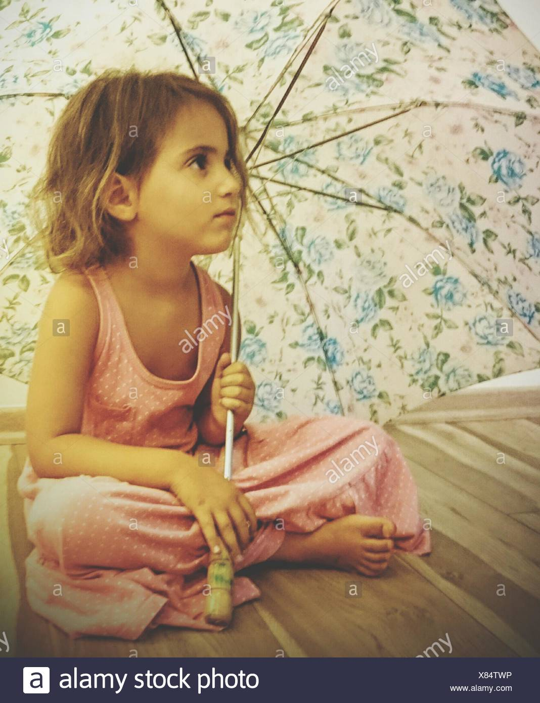 Close-Up Of Girl Holding Umbrella While Sitting On Bed At Home - Stock Image