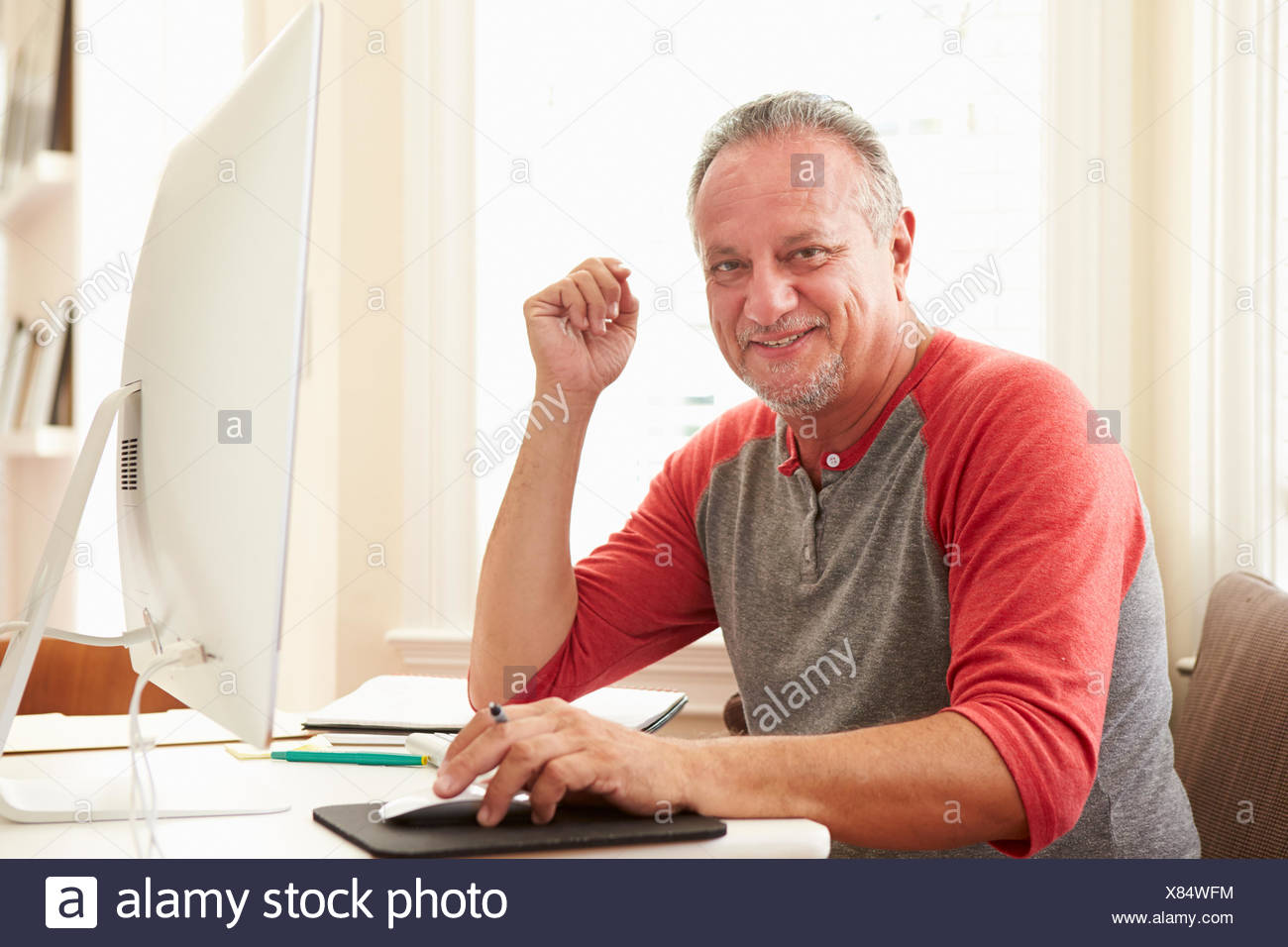 Portrait Of Senior Man Using Computer At Home - Stock Image