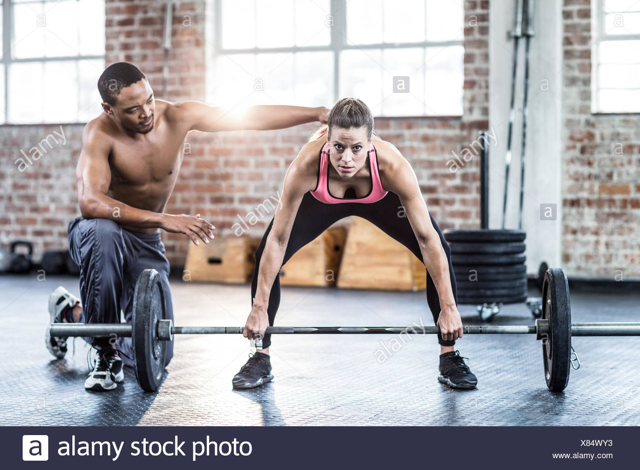 Trainer helping woman with lifting barbell Stock Photo