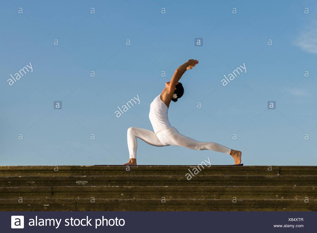 Young woman practising Hatha yoga, outdoors, showing the pose Anjaneyasana, Chandrasana, Half moon pose - Stock Image