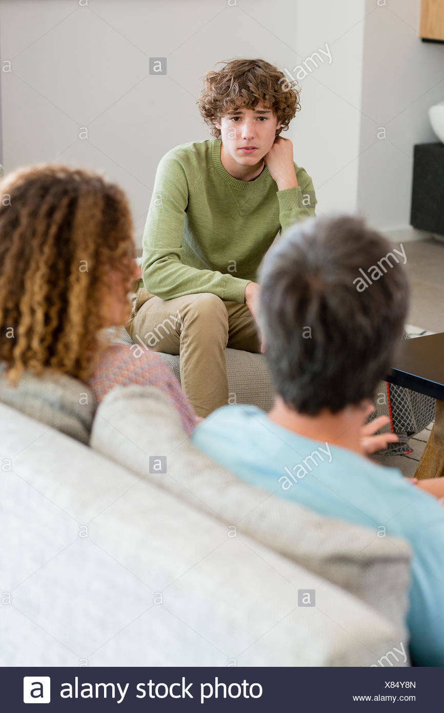 Family talking in a living room at home - Stock Image