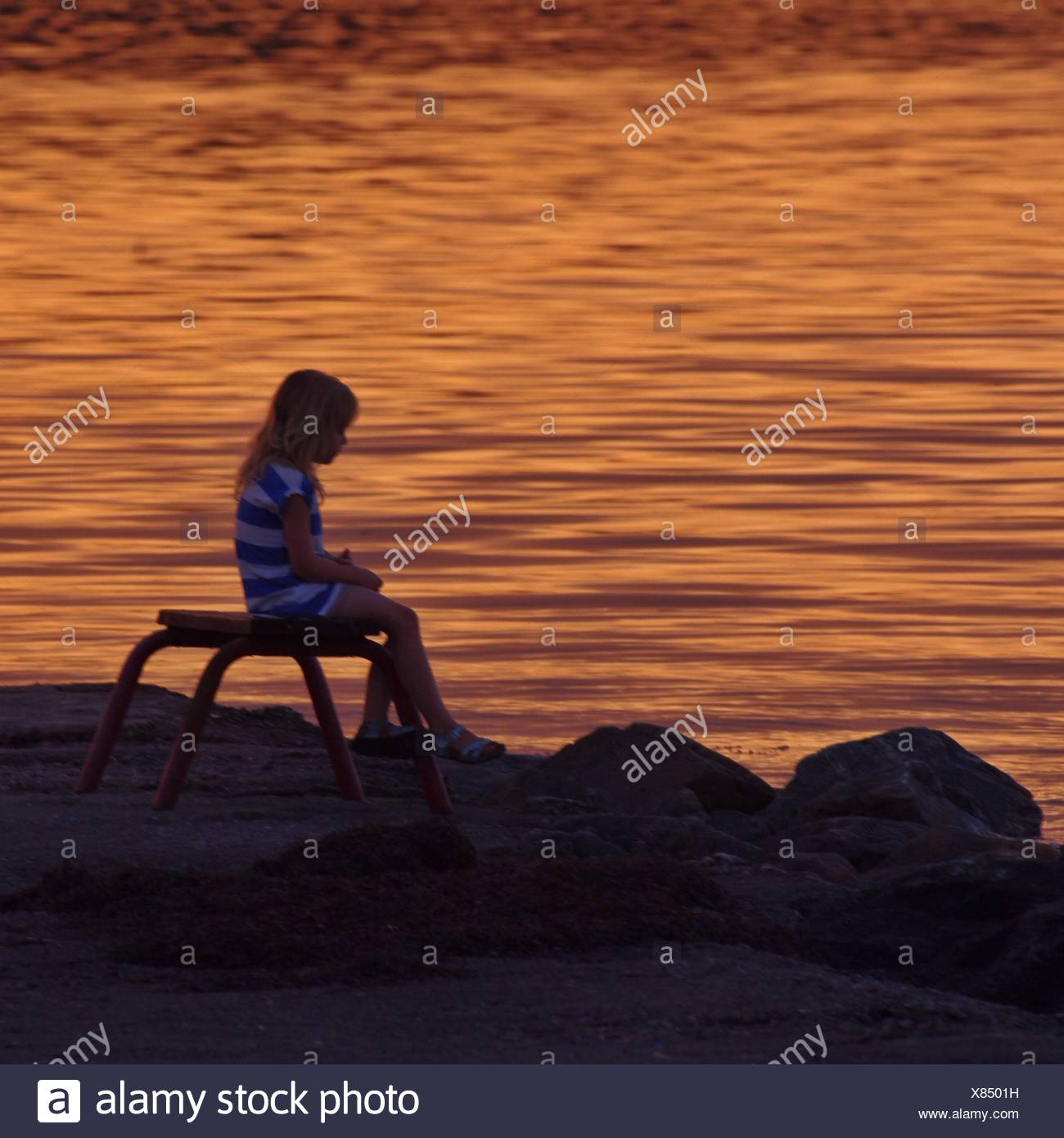 Girl Sitting On Bench By Water - Stock Image