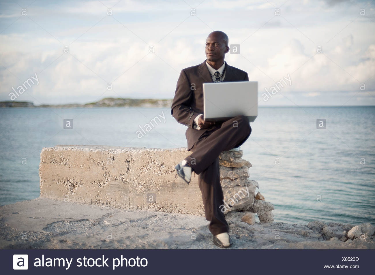 A Businessman With A Laptop Computer Sitting On A Rock Ledge At The Edge Of The Water; South Caicos Turks And Caicos Islands - Stock Image