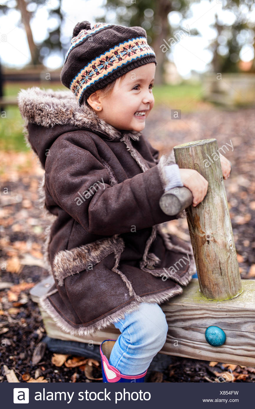 Happy little girl on a playground in autumn Stock Photo