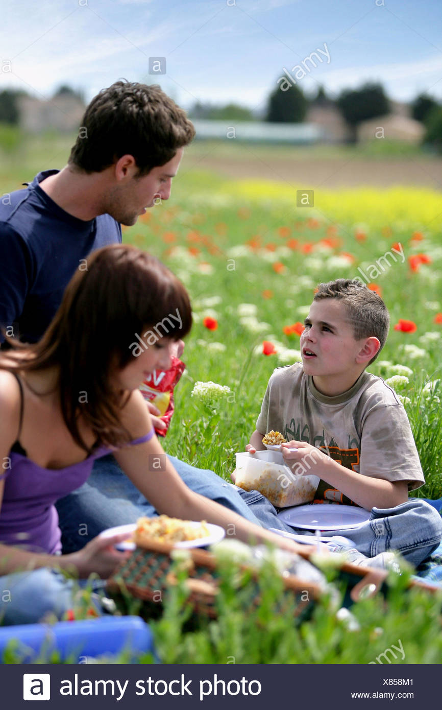 Family having a picnic in a poppies yard - Stock Image