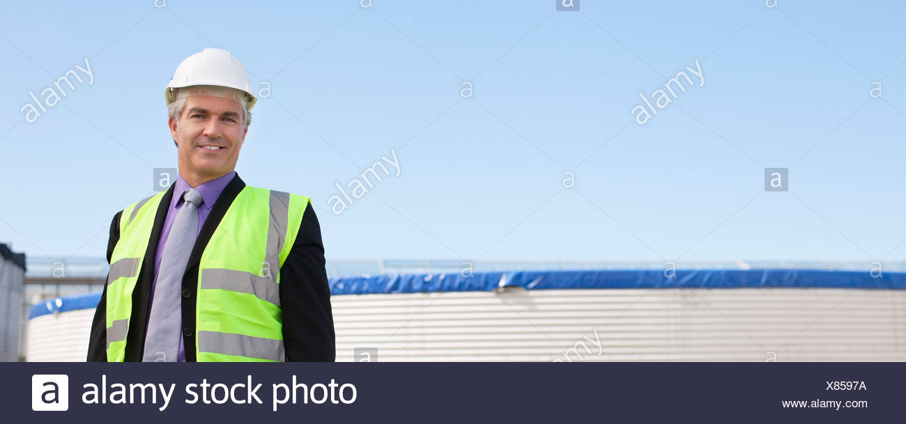 Businessman in safety gear standing outdoors - Stock Image