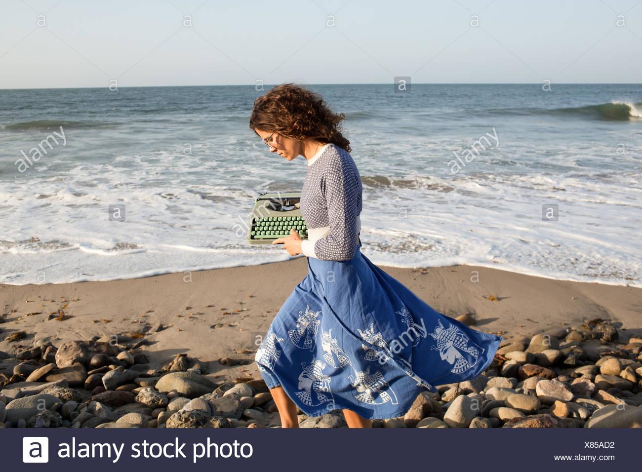 Woman walking along beach with typewriter - Stock Image