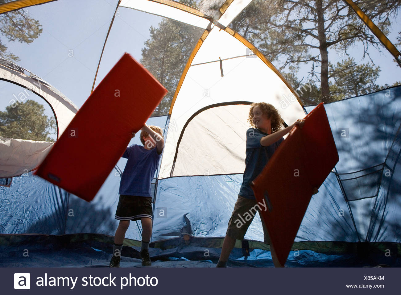 Two boys playing with inflatable mattresses in a tent - Stock Image