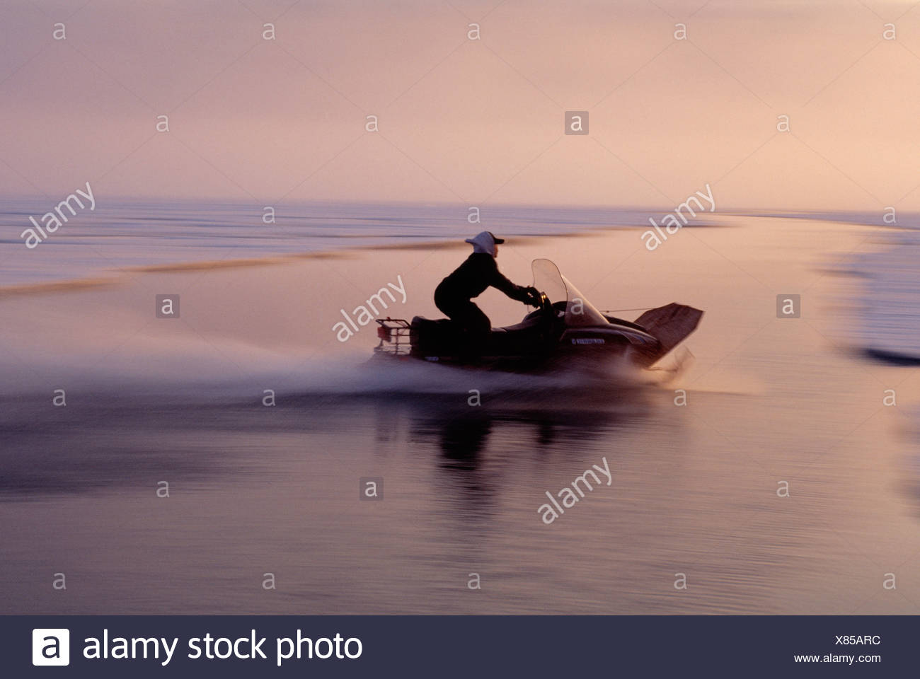 Inuit hunter snowmobile driving over open water, Baffin Island, Nunavut, Canada. - Stock Image