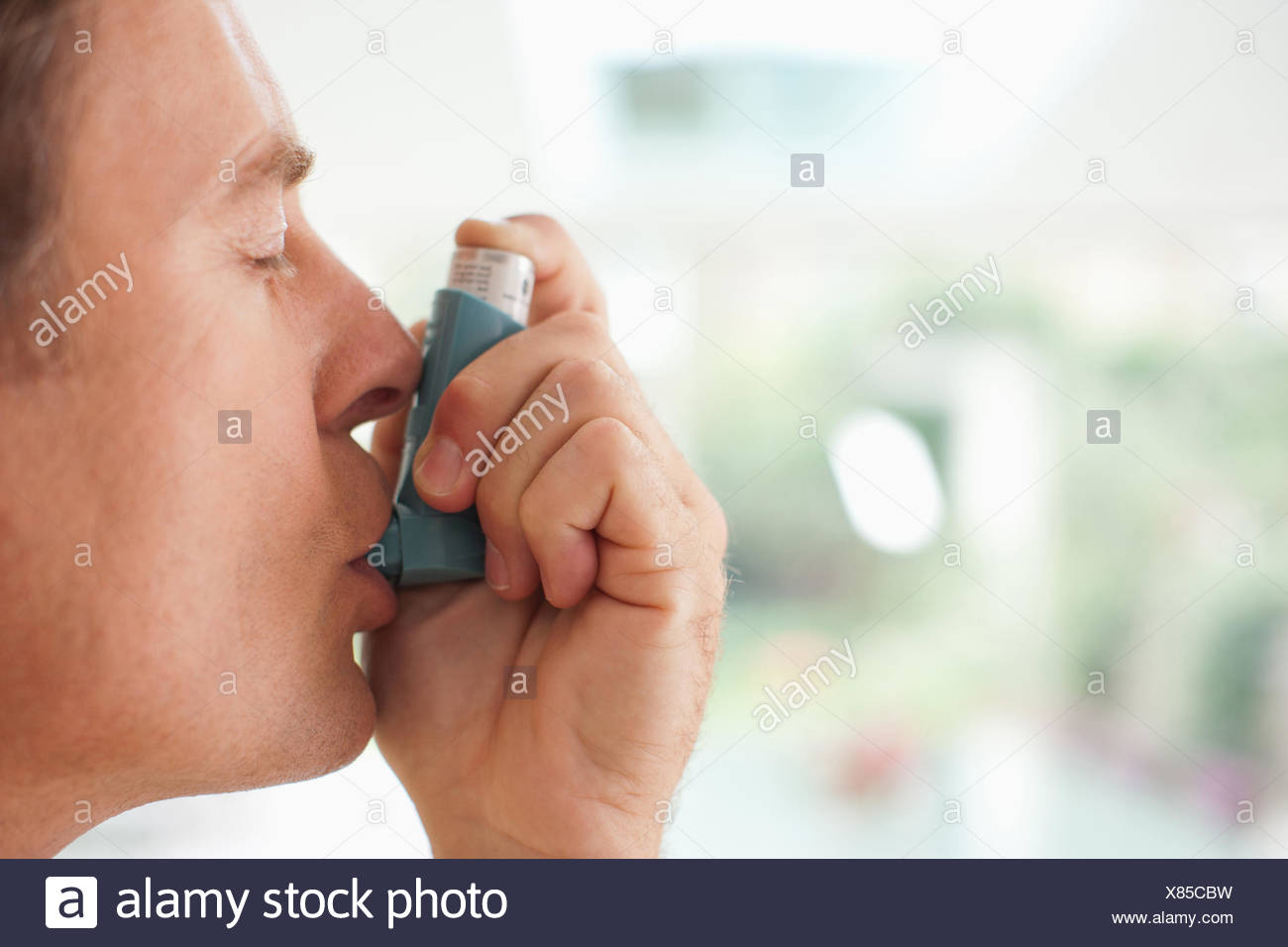 Man about to use asthma inhaler - Stock Image