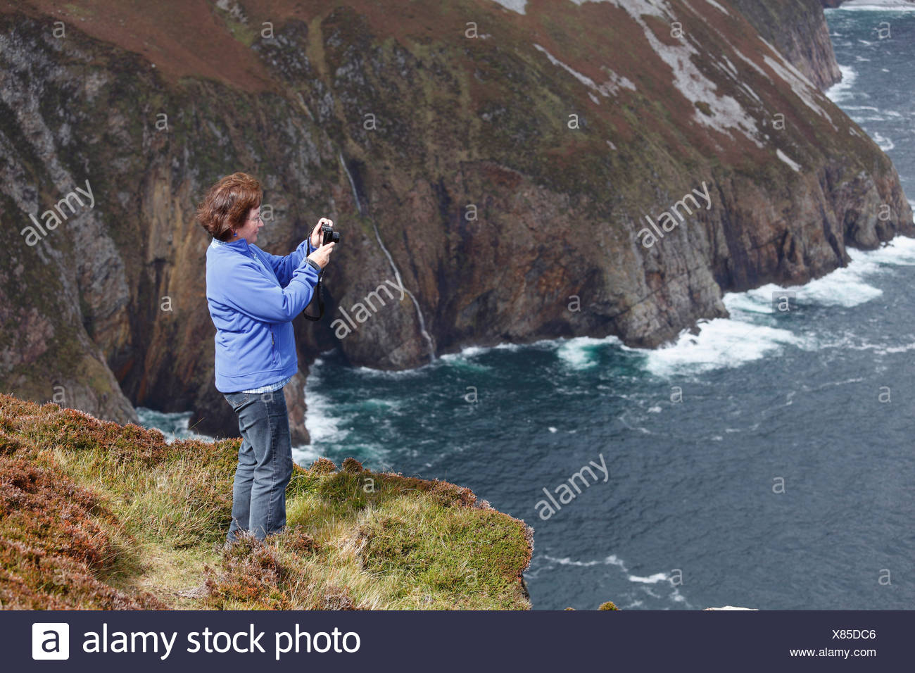 Woman taking pictures with a digital compact camera, at the cliffs of Slieve League, County Donegal, Ireland, Europe - Stock Image