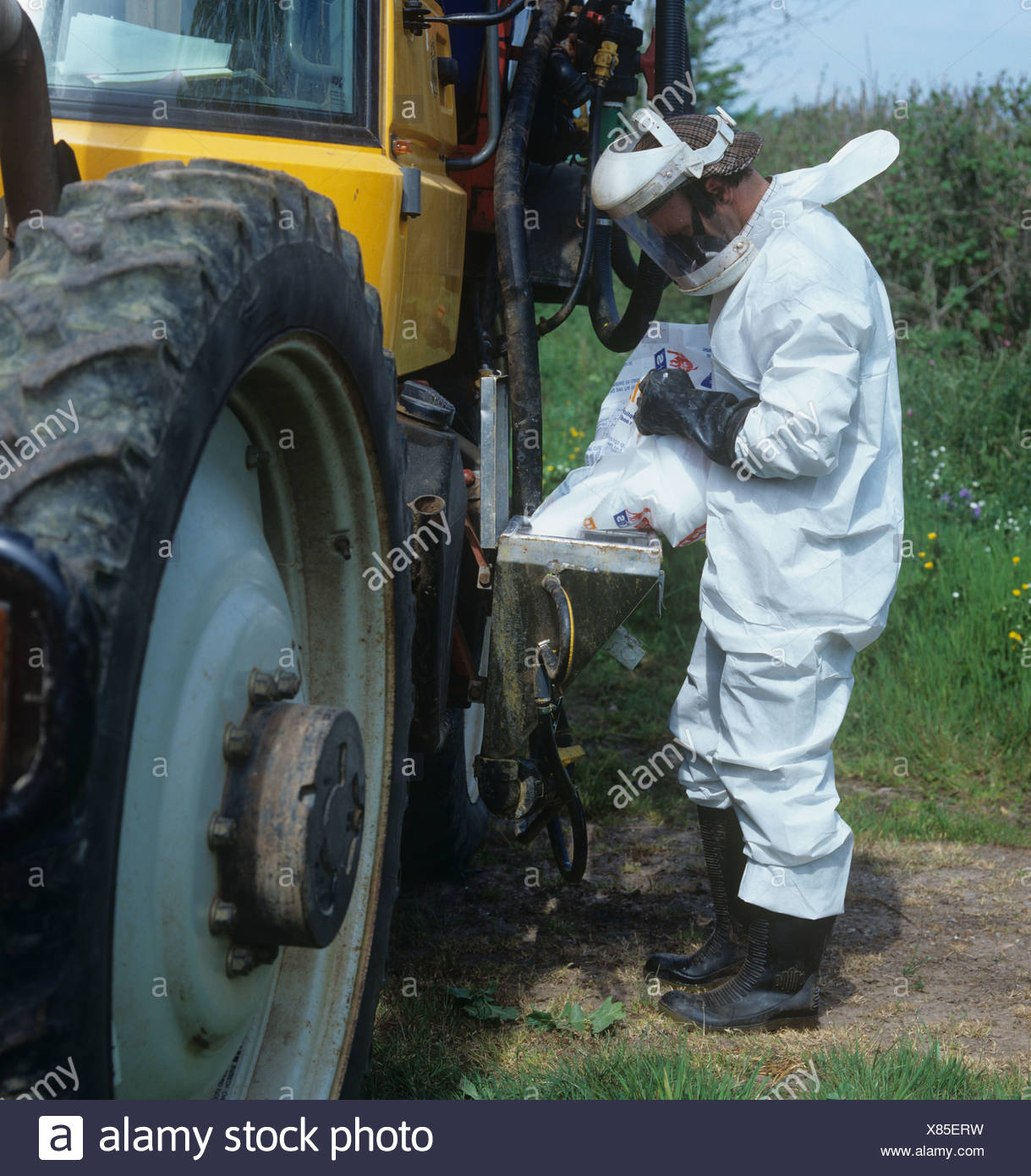 Worker wearing full protective gear filling tank on Gem 2000 sprayer mounted on Fastrac tractor - Stock Image