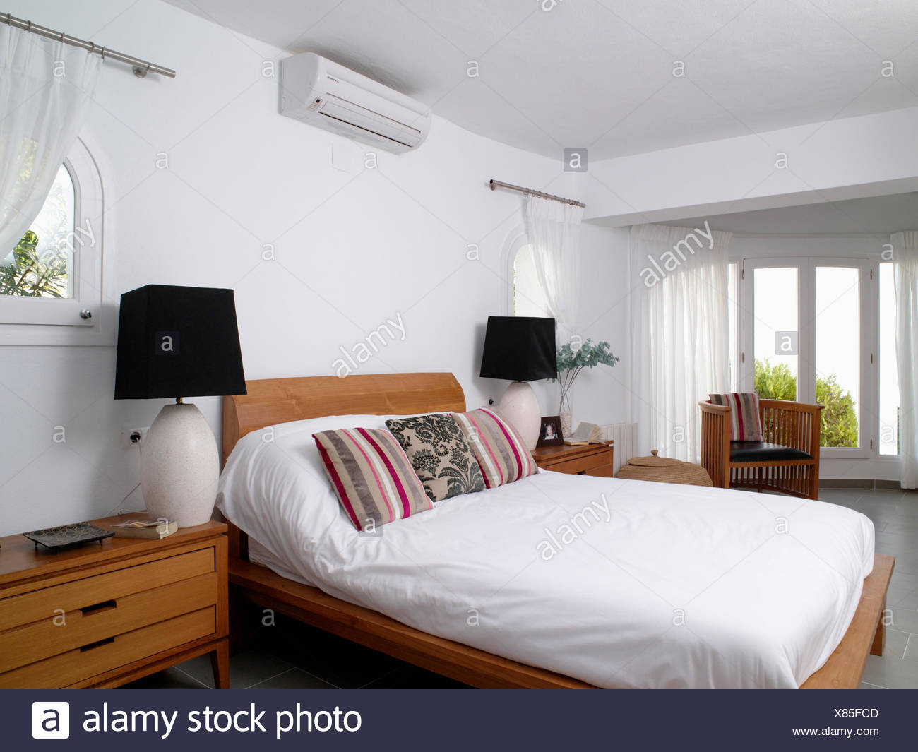 Small air-conditioning unit above bed with white duvet and ...