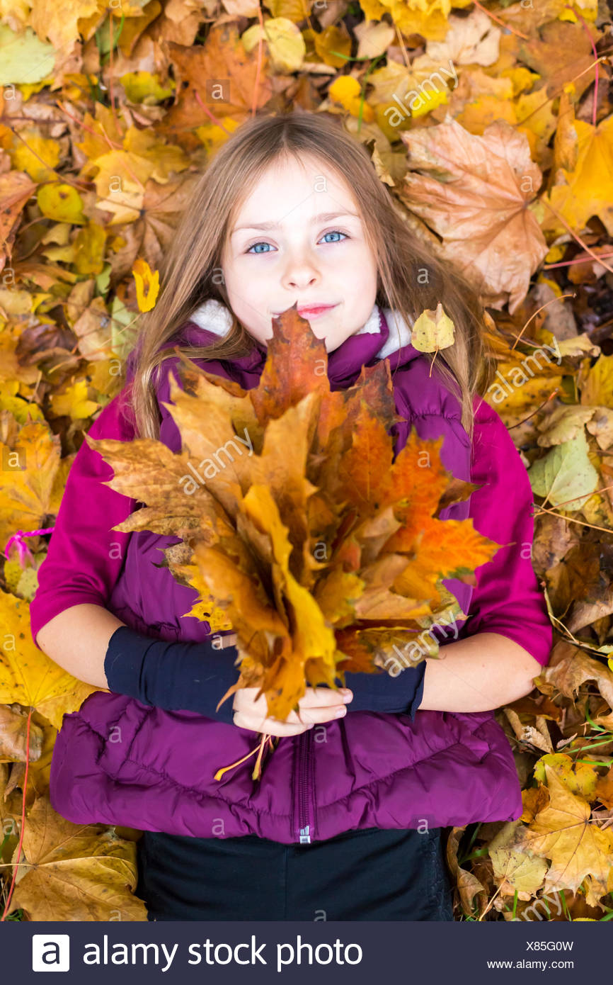 Portrait of girl lying on the ground holding bunch of autumn leaves Stock Photo