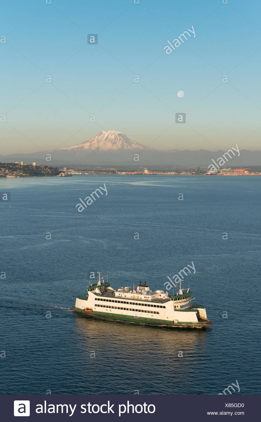 The Washington State Ferry sails in front of Mount Rainier and a full moon at sunset. - Stock Image