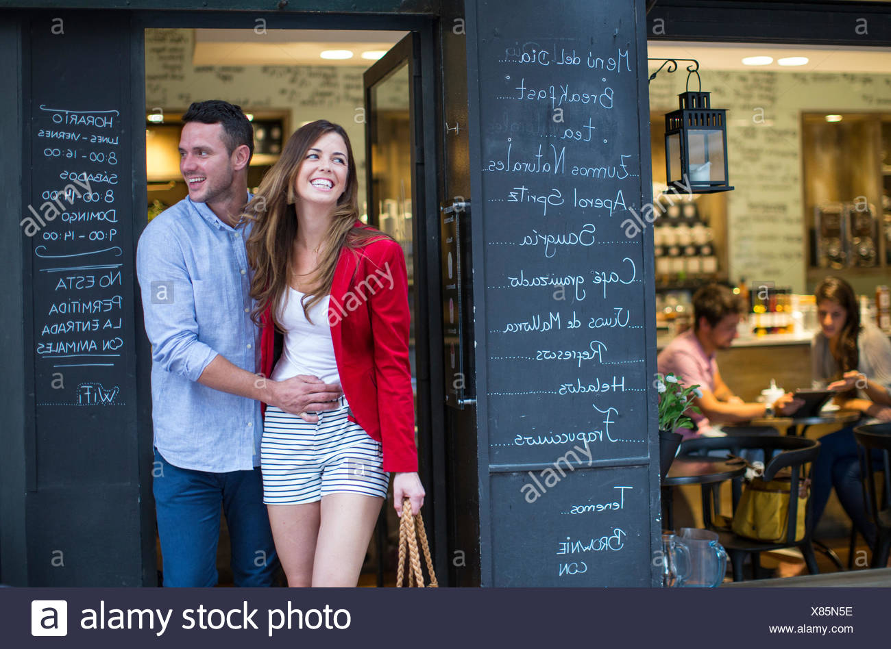 Romantic couple leaving cafe - Stock Image