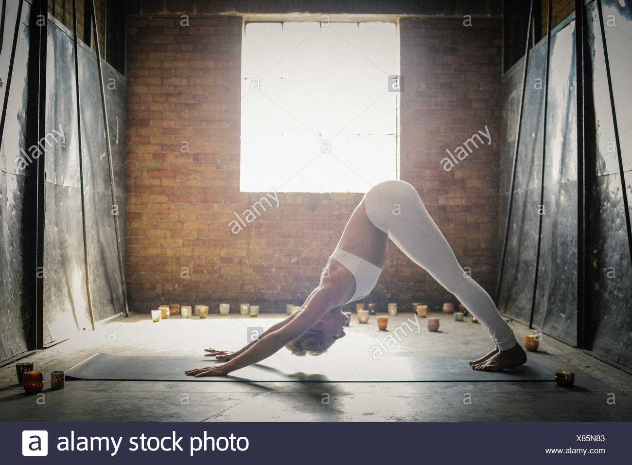 A blonde woman bending down on the floor surrounded by candles, stretching. A window in the brick wall behind her. - Stock Image