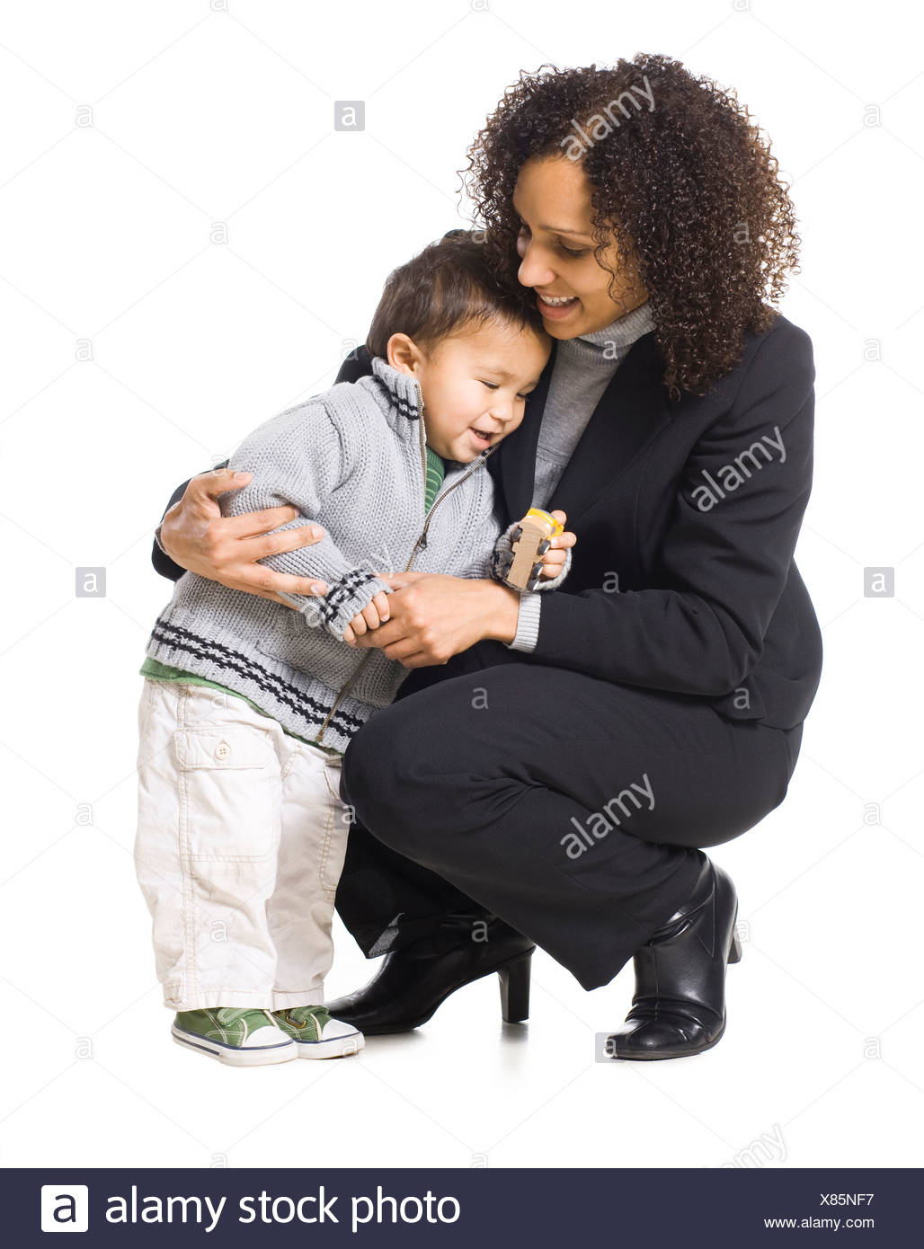 Mother embracing son (18-23 months), studio shot - Stock Image