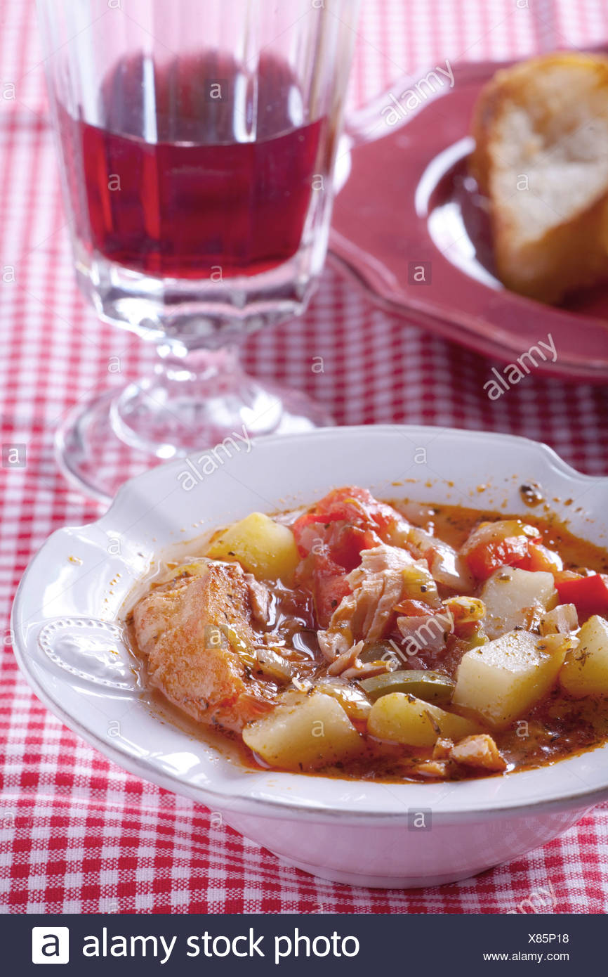 Basque fish soup wot a glass of red wine behind Stock Photo