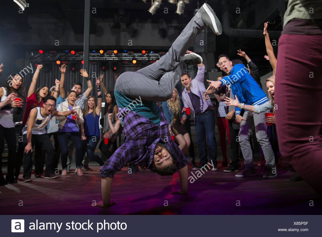 Crowd watching and cheering break dancer - Stock Image