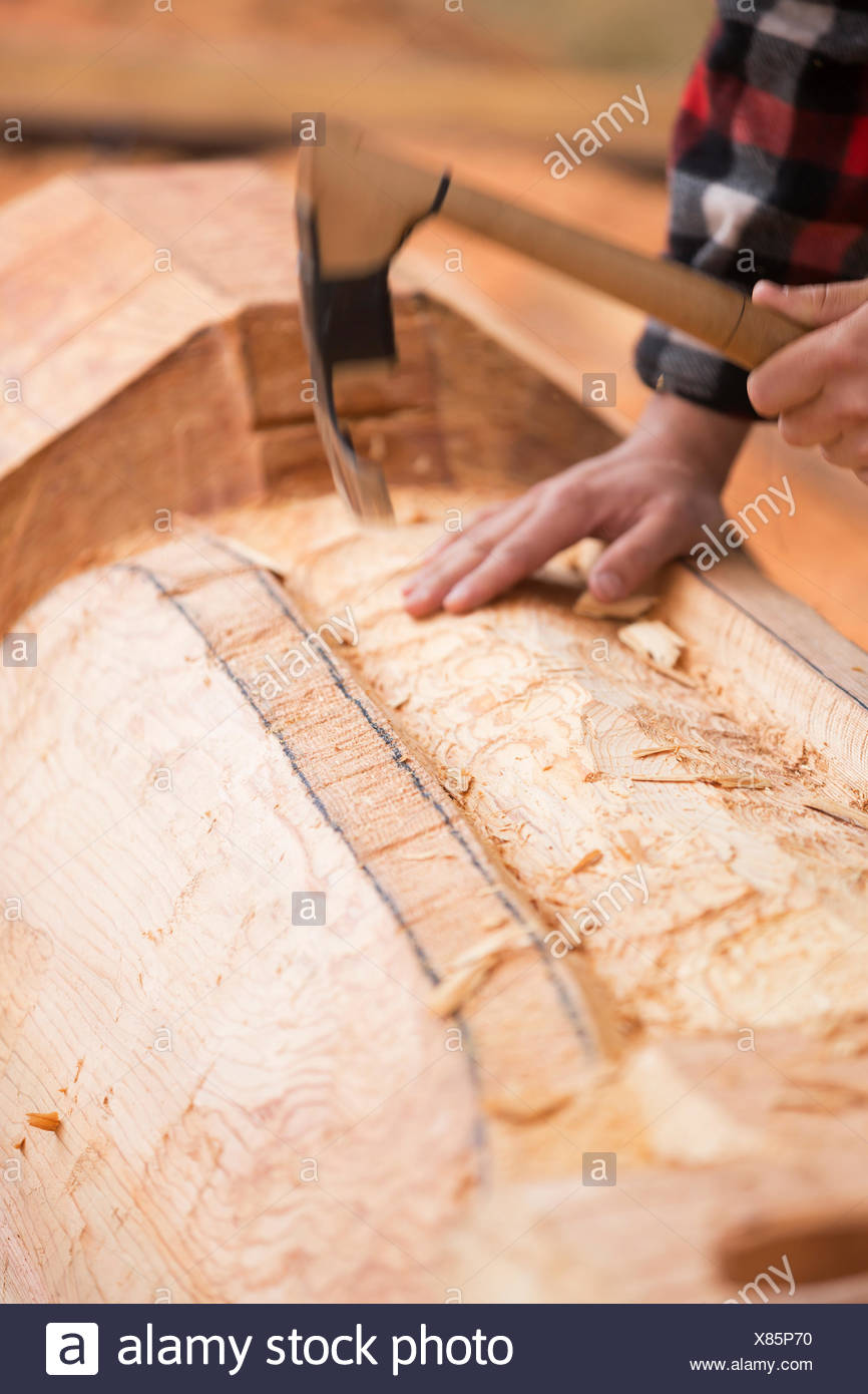 A first nations carver works with an adze roughing out a Thunderbird motif on a pole.  Comox, Vancouver island, British Columbia, Canada. - Stock Image