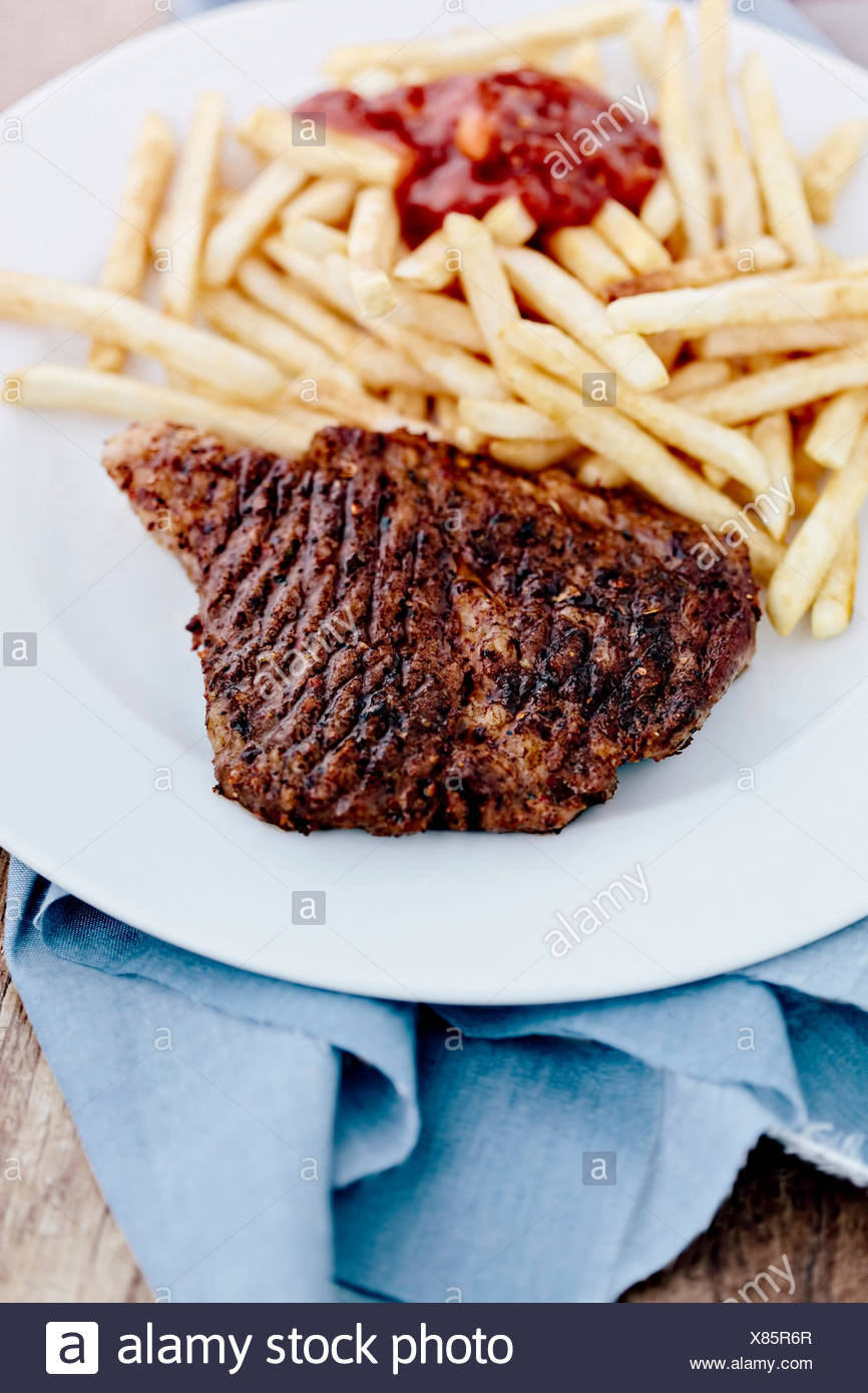 French fries and ketchup close up with steak - Stock Image