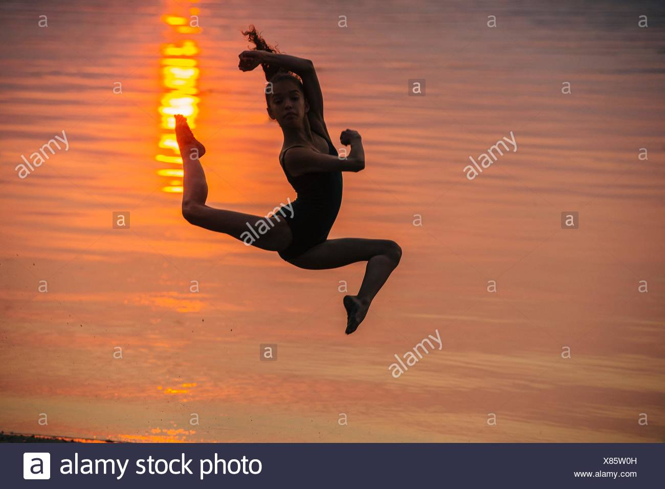 Side view of girl in silhouette by ocean at sunset leaping in mid air, legs apart looking at camera - Stock Image