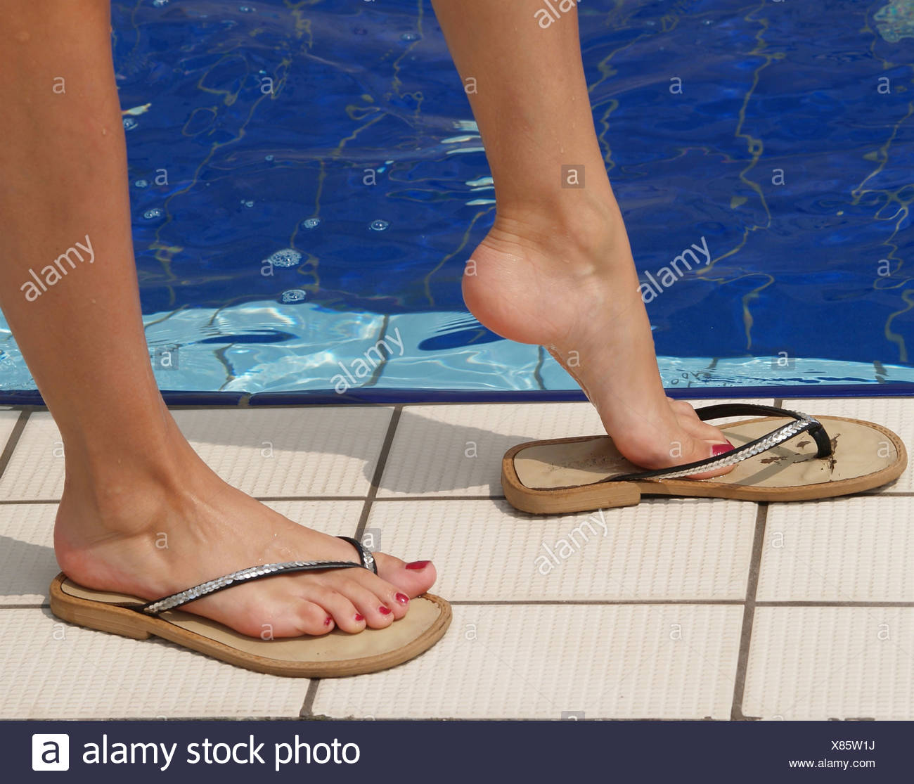 8b086f016 young woman s feet with varnished toenails in flip-flops at the edge of a swimming  pool