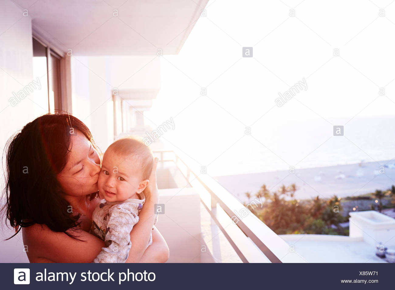 Portrait of mid adult mother and baby son on apartment balcony - Stock Image