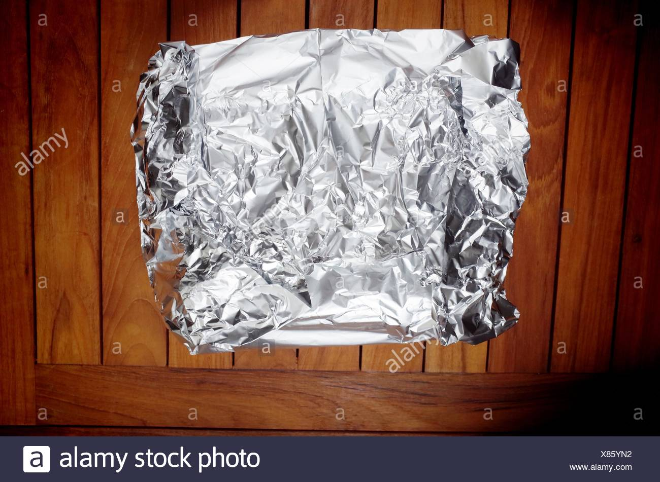 High Angle View Of Aluminum Foil Wrapped Box On Table - Stock Image