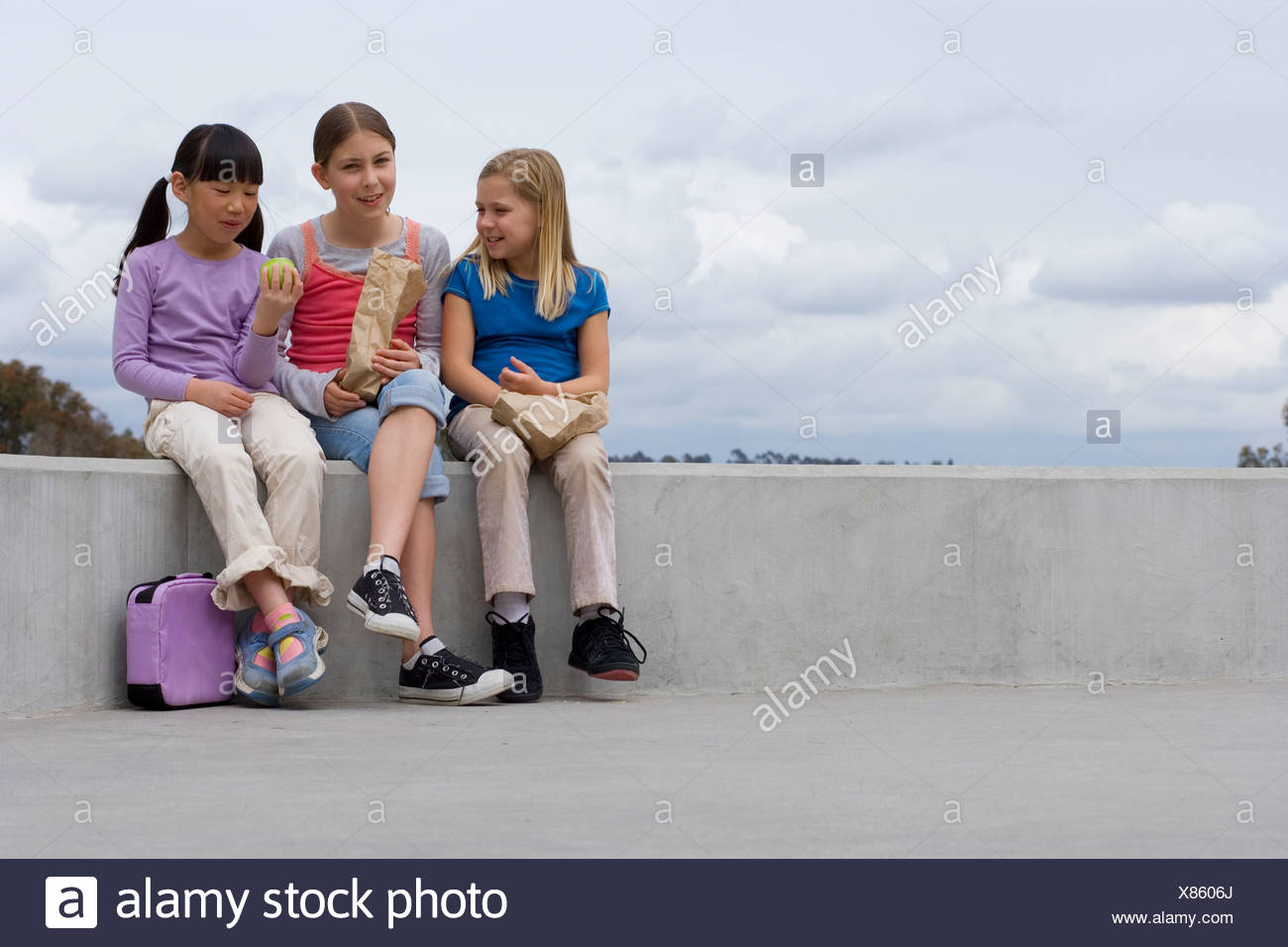 Three girls 9 11 sitting on wall outside school eating packed lunch smiling - Stock Image