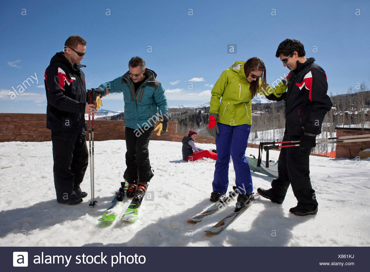Mature man and young woman with ski instructors on ski slope - Stock Image