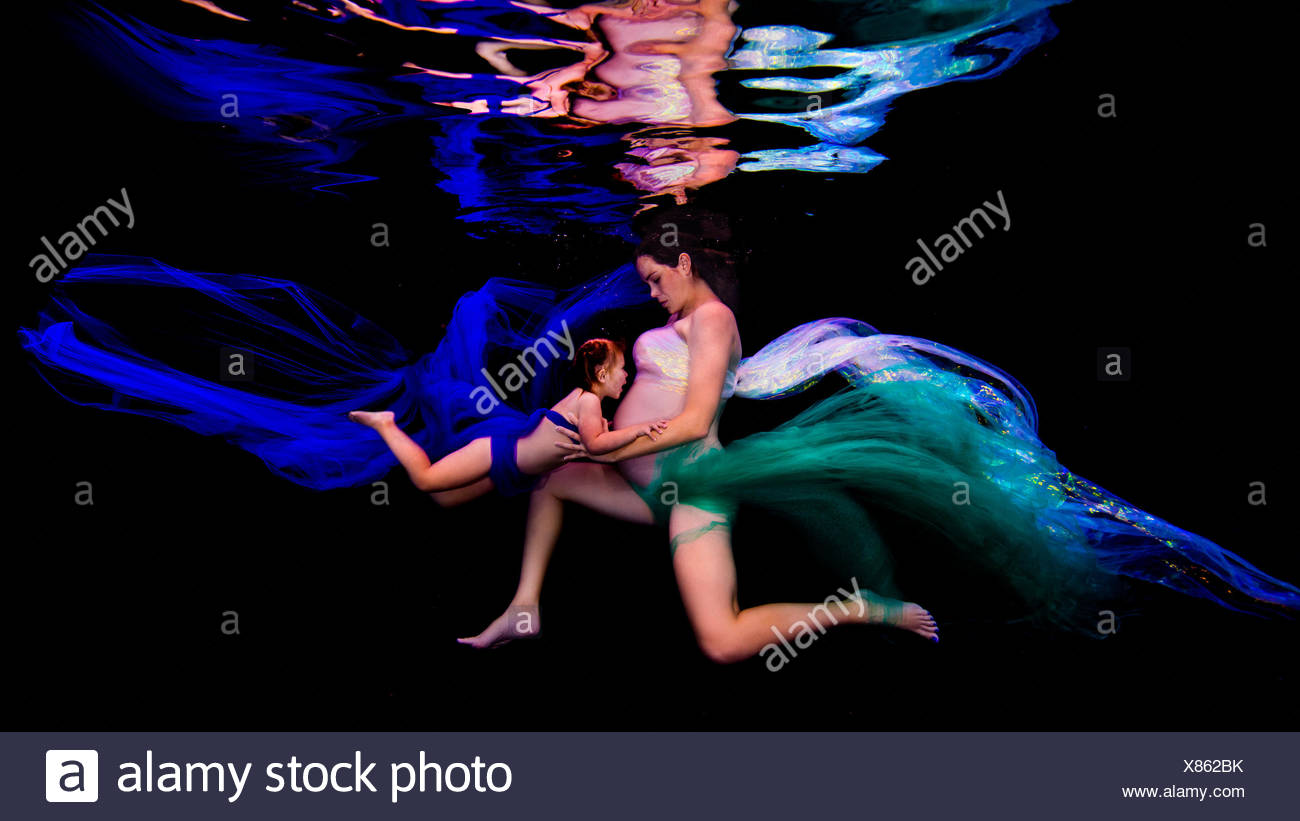 Underwater view of young pregnant woman and girl poised together in darkness - Stock Image