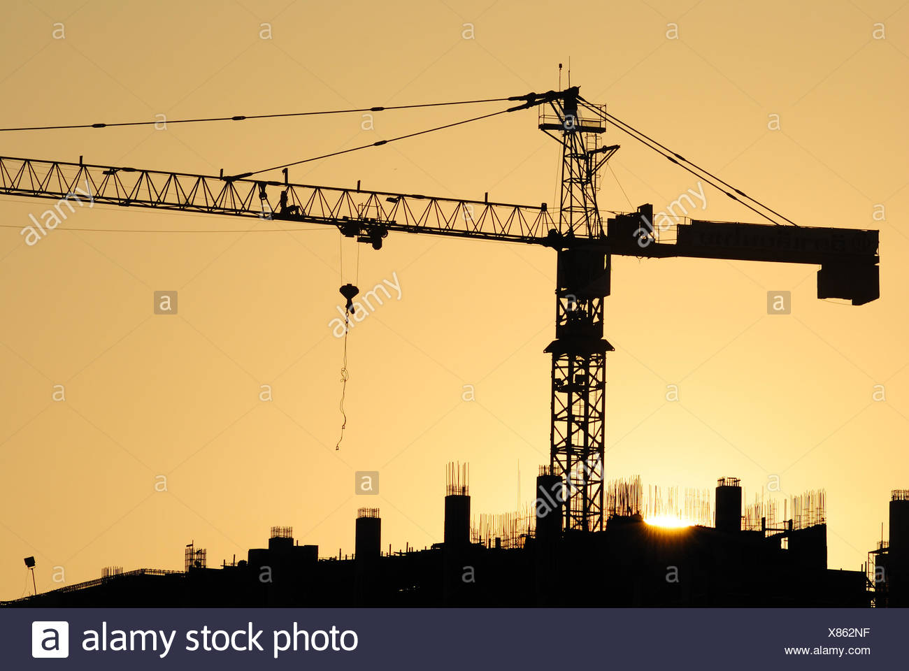 Silhouette Crane At Construction Site During Sunset - Stock Image