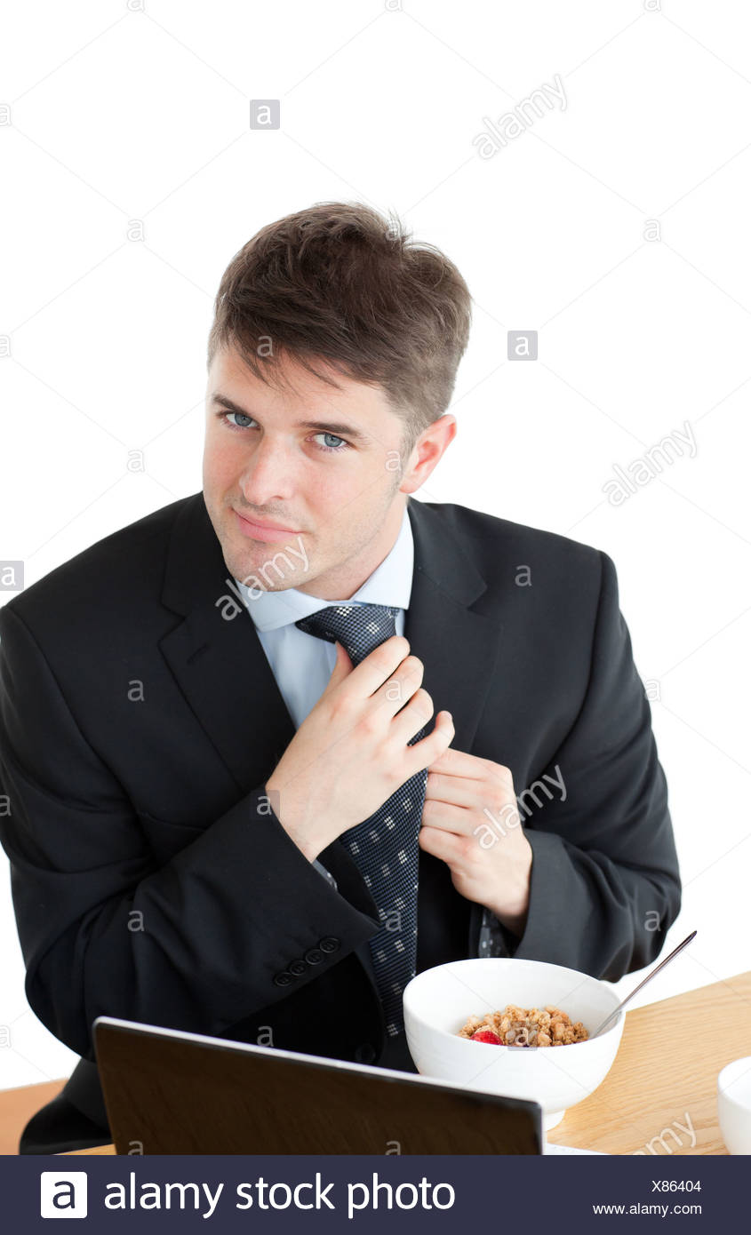 Elegant businessman having breakfast and touching his tie in front of his laptop Stock Photo