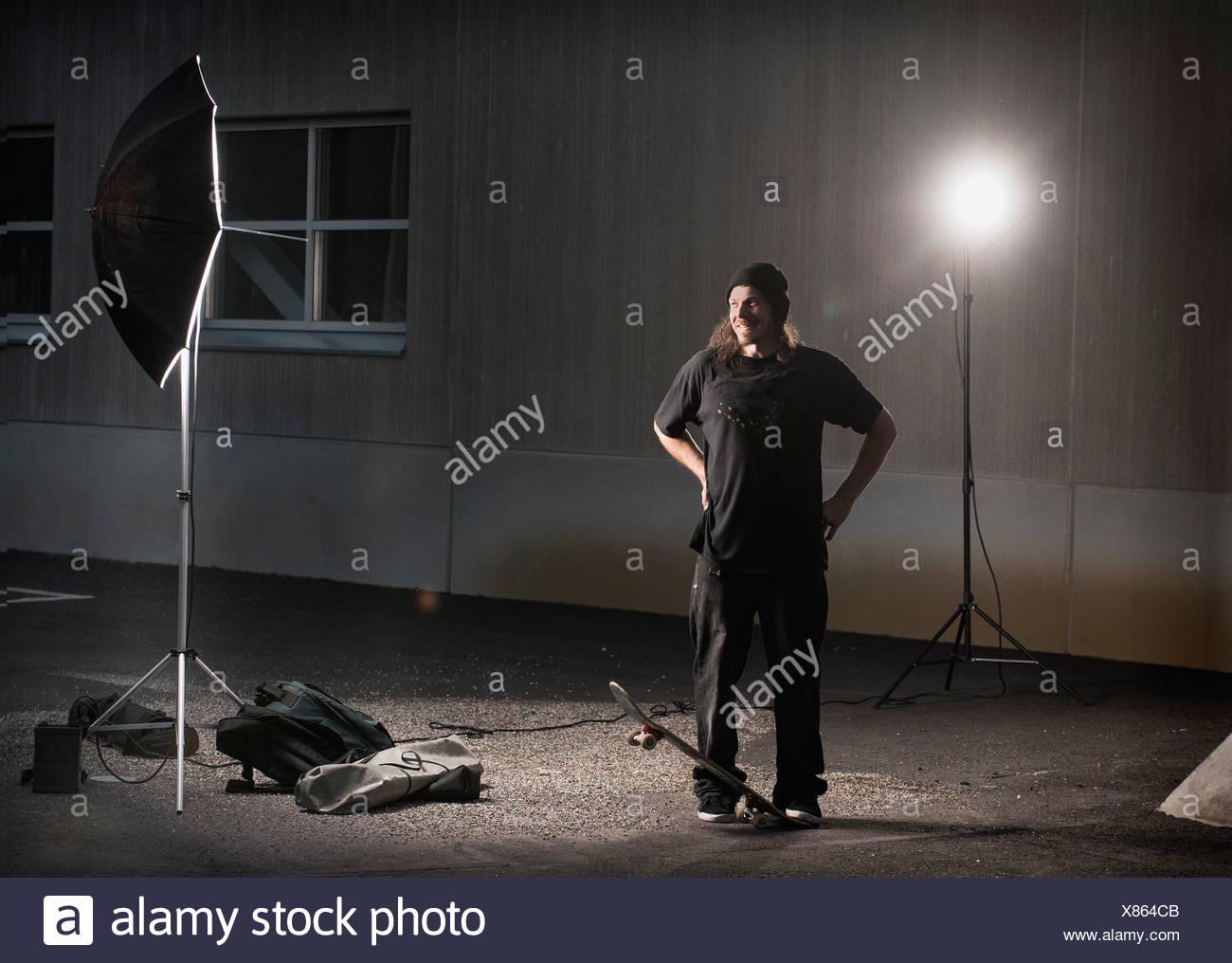 Skater standing under photo lights - Stock Image