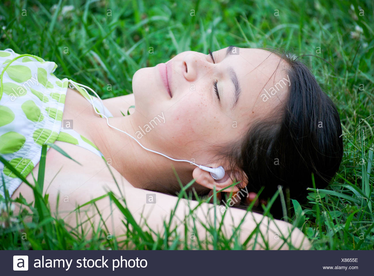 Girl (10-11 years) with in-ear headphones lying in grass - Stock Image