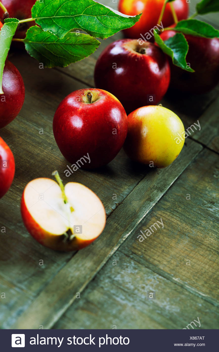red apples with leaves on wooden table - Stock Image