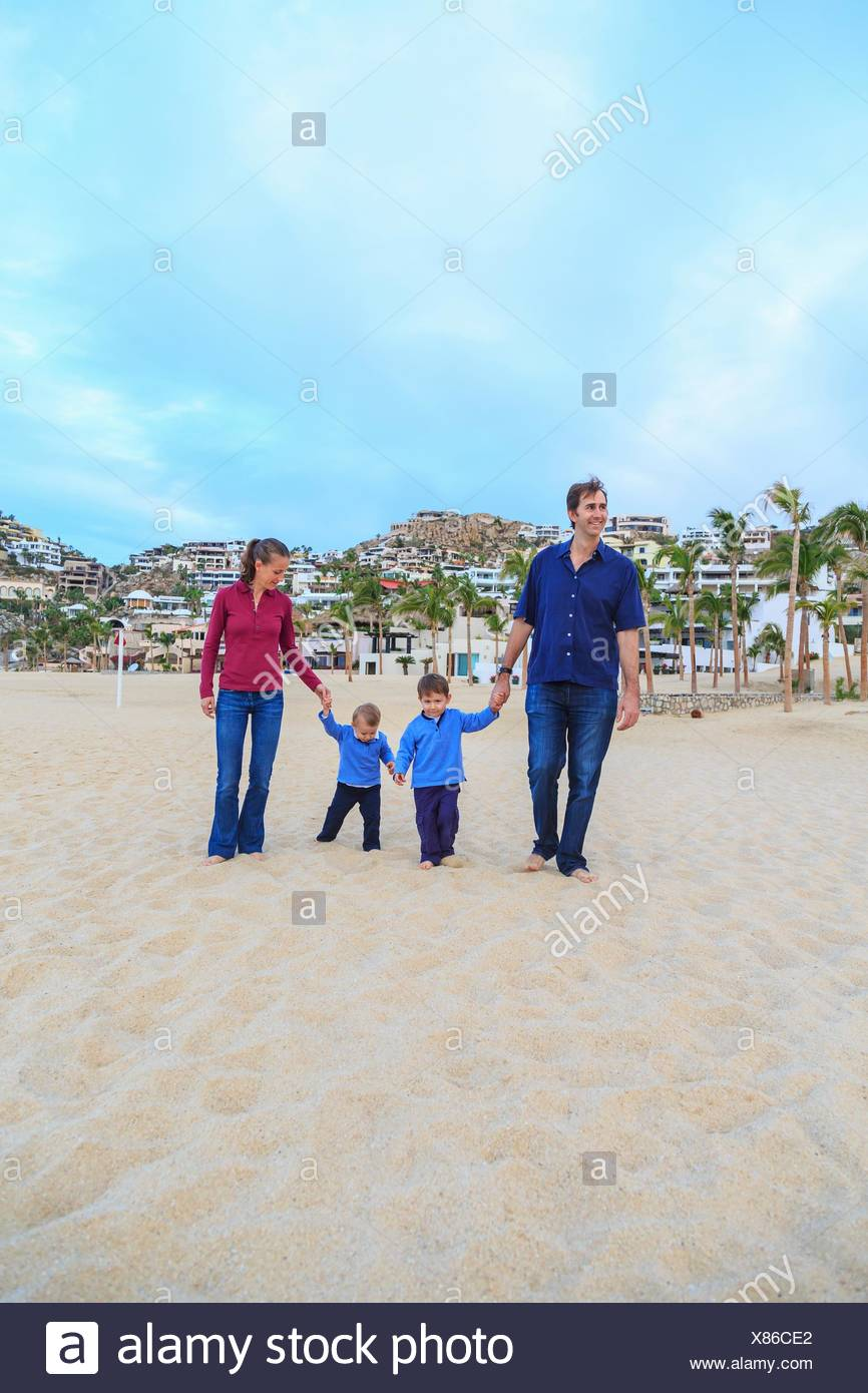 Young family, walking on beach, holding hands - Stock Image