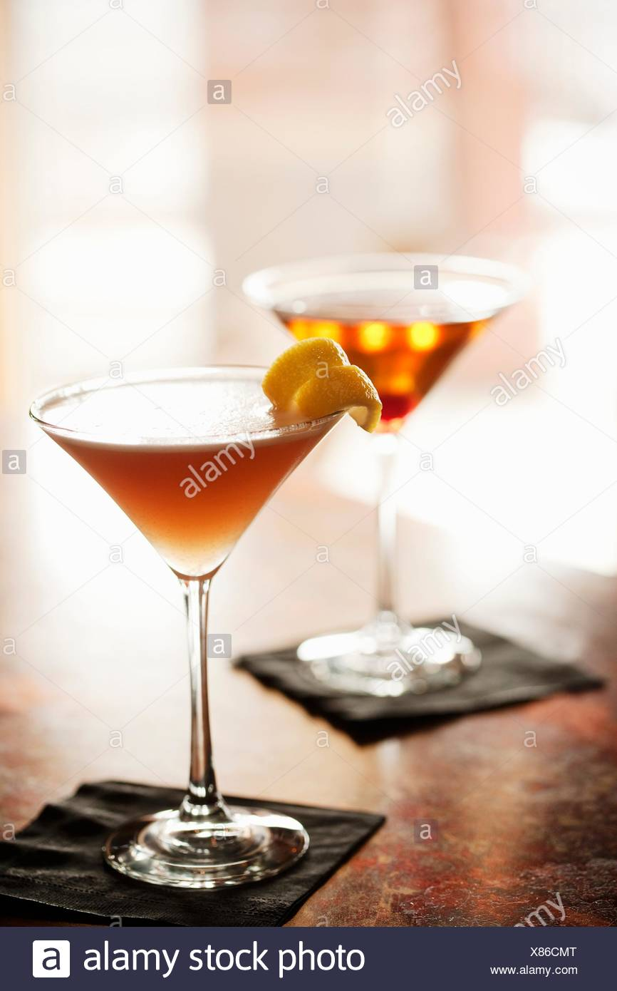 Two Cocktails in Stem Glasses on a Bar (Aviation Cocktail and Manhattan) - Stock Image